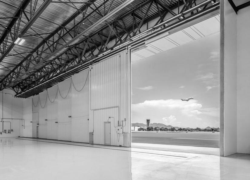 Scottsdale Airport Hanger with a plane flying by.